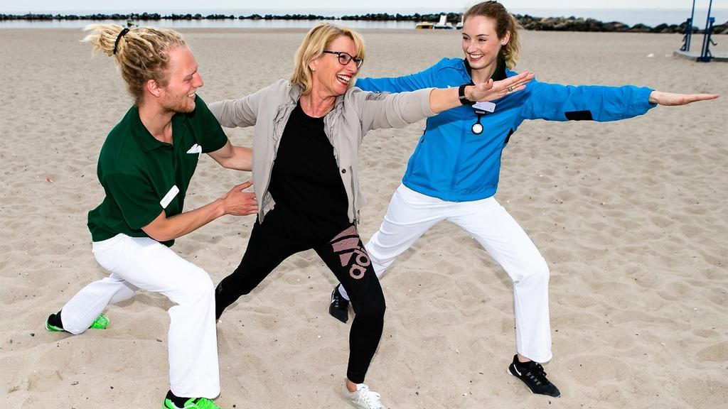 Zwei Frauen und ein Mann machen Yoga am Strand