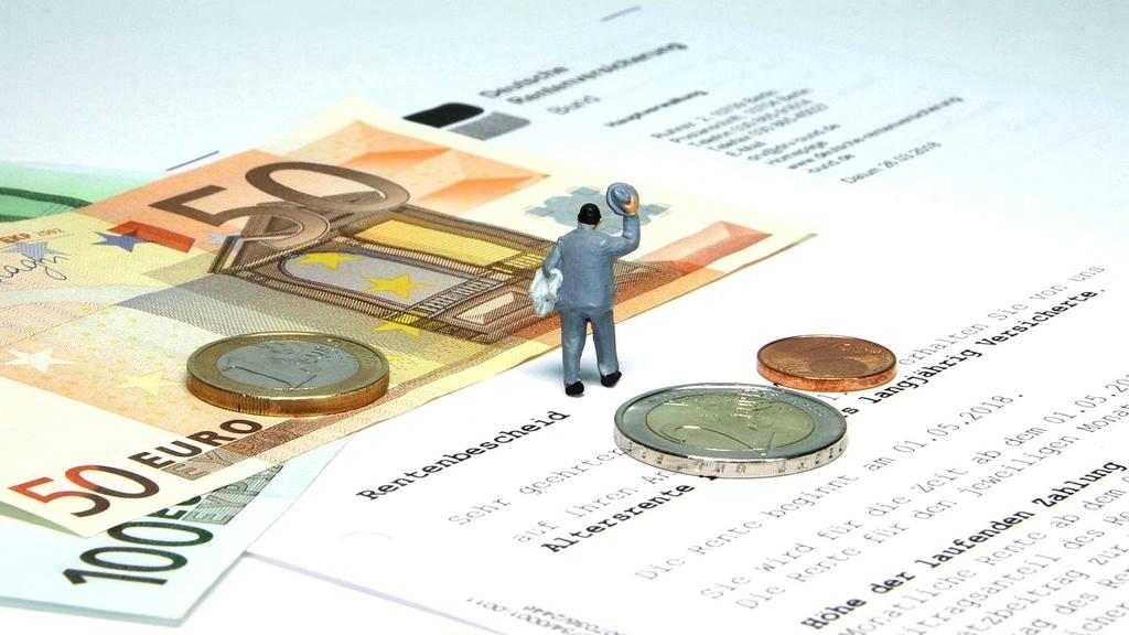 Bild: Rentenbescheid, Geld und Miniaturnachbildung eines Menschen liegen auf einem Tisch