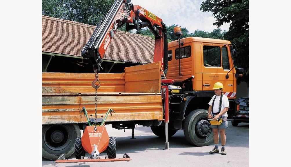 Bild: Bauarbeiter amLkw-Ladekran mit Funkfernsteuerung