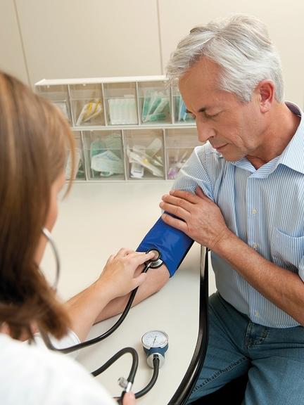 Junge Frau misst älterem Herrn den Blutdruck