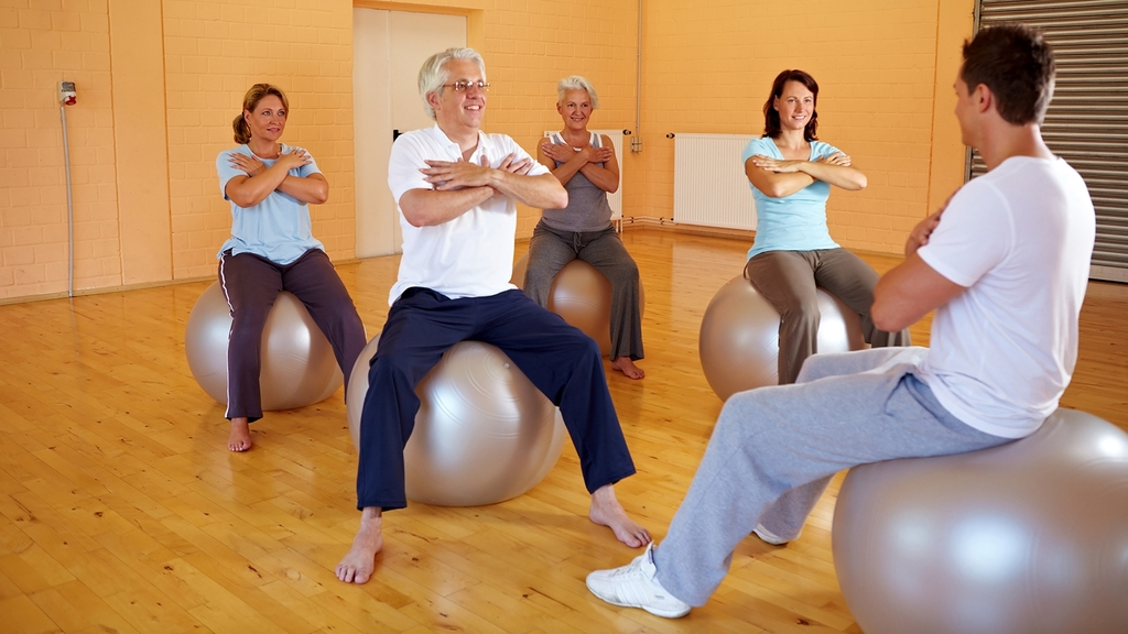 Personen sitzen auf dem Gymnastikball und führen eine Sportübung aus.