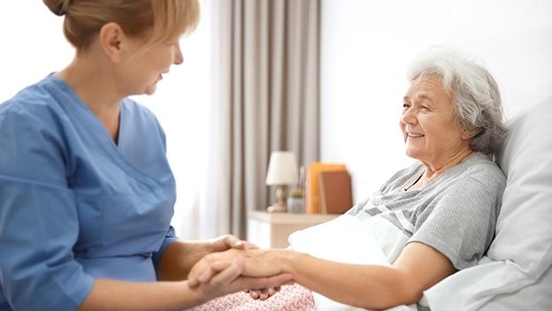 Pflegeperson mit Pflegebedürftiger am Bett