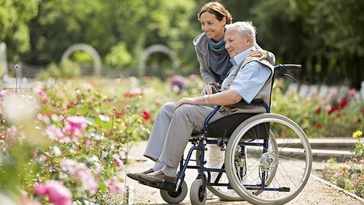Pflegerin mit Senior im Rollstuhl