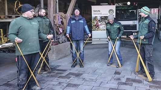 Männer führen im Stehen eine Rückenübung mit dem Theraband aus