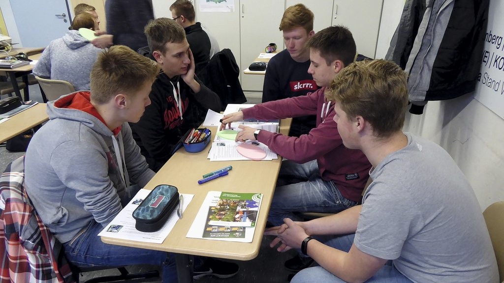 Jugendliche sitzen am Tisch und schauen sich Unterlagen an