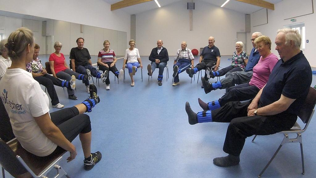 Senioren sitzend im Kreis mit Trittsicher-Manschetten