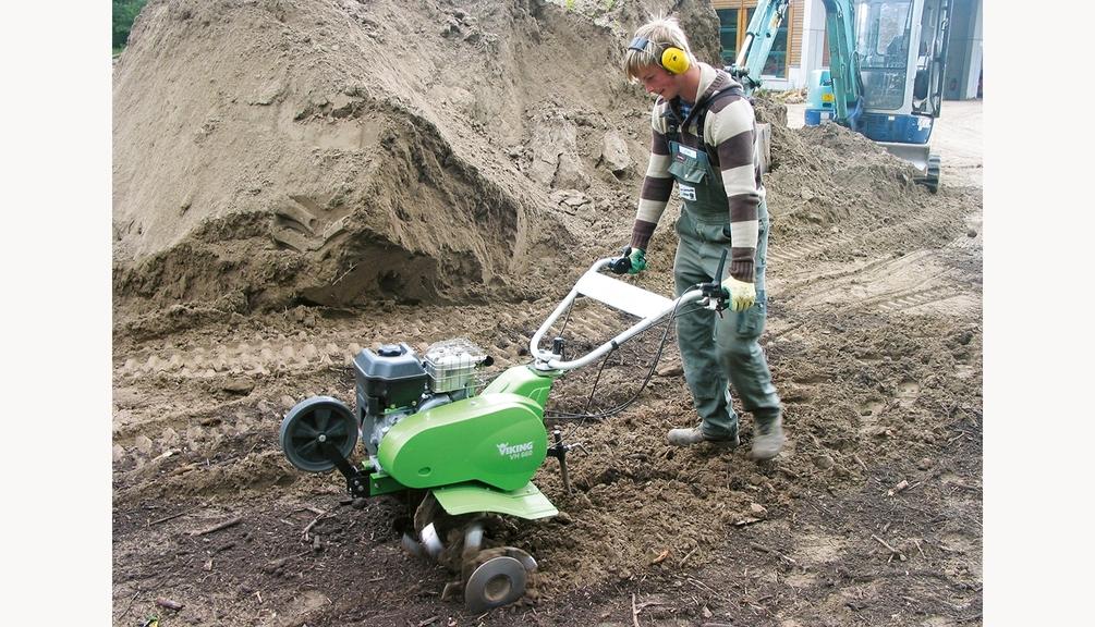 Bild: Arbeiter in Schutzkleidung bei der Bodenbearbeitung mit einer triebradlosen Motorhacke