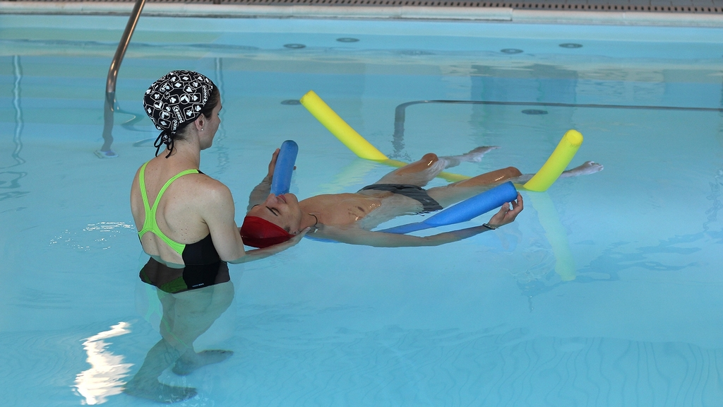Zwei Personen im Schwimmbecken; ein Mann liegt auf dem Wasser auf Schwimmnudeln, eine Frau steht im Wasser an seinem Kopfende und stützt seinen Kopf