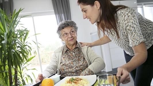 Pflegekraft mit Seniorin beim Essen
