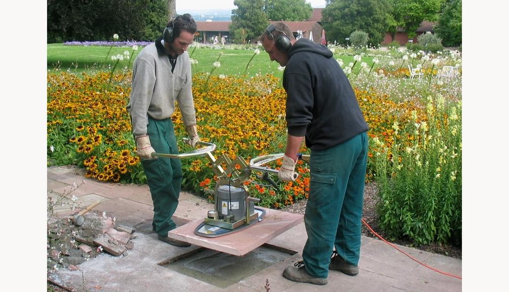 Bild: Zwei Arbeiter bei Erdbauarbeiten mit einem Vakuumhebegeräte