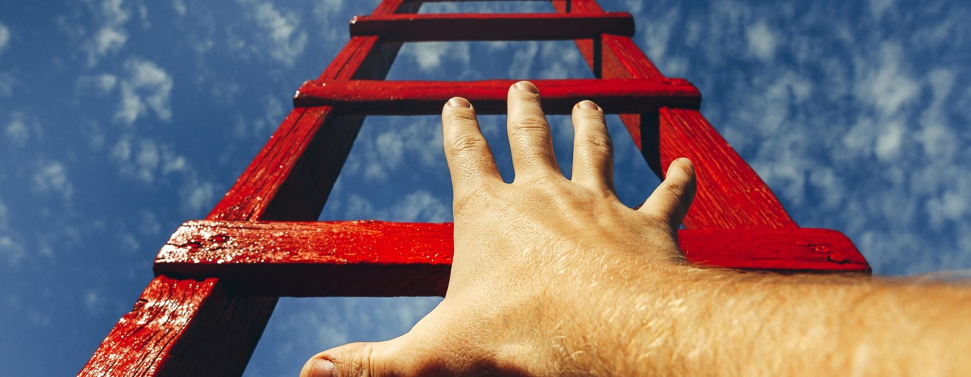 Hand greift nach einer Leiter nach oben