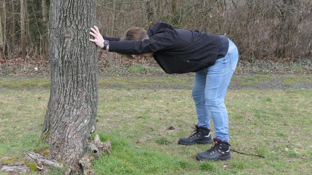 Junger Mann macht Bewegungsübung in der Natur an einen Baum abstützend.