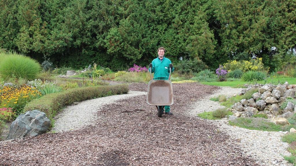 Gärtner mit Schubkarre in einer Parkanlage