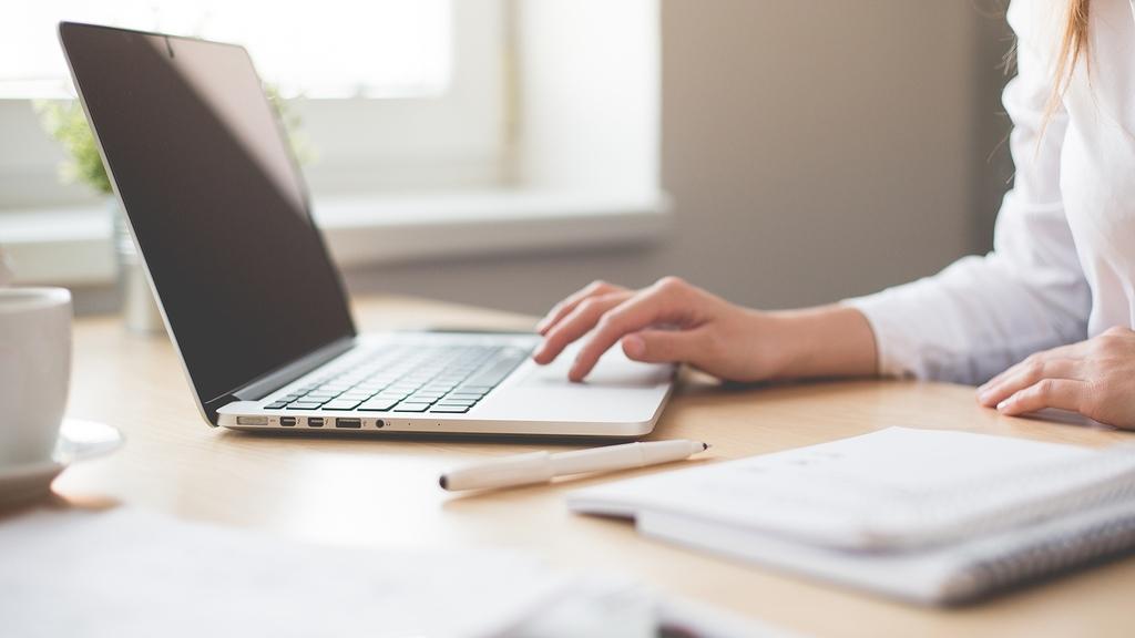 Frau arbeitet am Laptop auf dem Schreibtisch