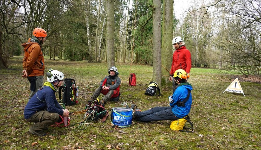 Fünf Teilnehmer der Schulung für Seilklettertechnik mit Ausrüstung sitzen im Wald
