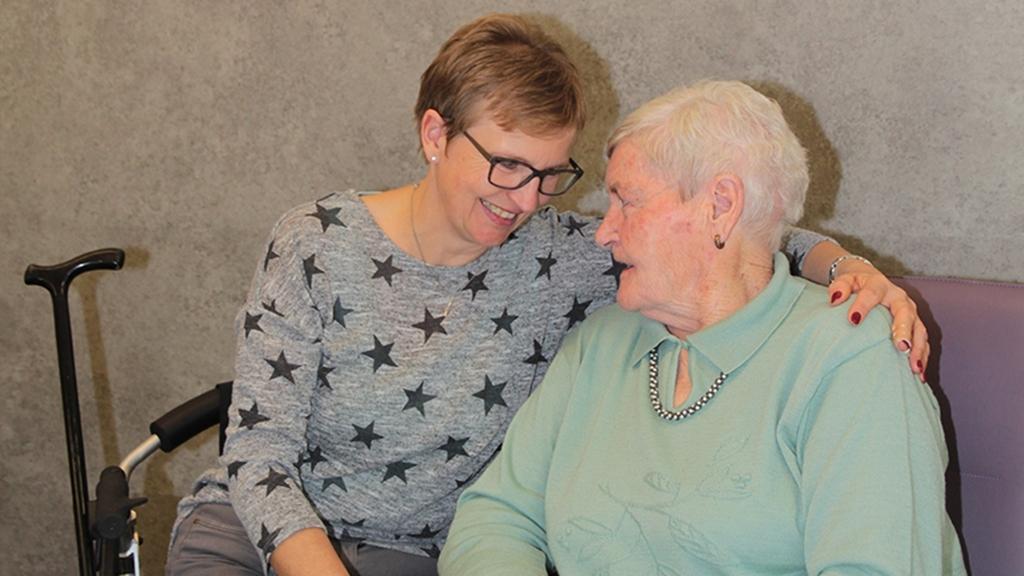 Eine jüngere und eine ältere Frau sitzen nebeneinander und lächeln sich an. Dabei hat die jüngere Frau ihren Arm um die ältere Frau gelegt.