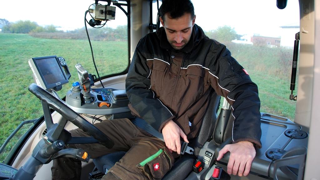 Ein junger Mann auf einem Traktor schnallt sich an