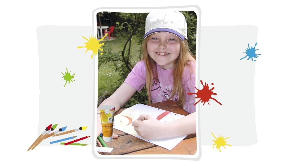 Lachendes Mädchen mit Cappy zeichnet - außerdem zu sehen Kleckse, Pinsel und Buntstifte