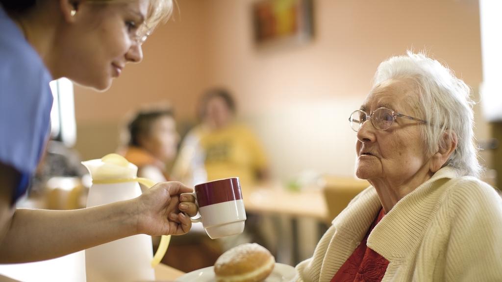 Pflegerin mit Seniorin im Pflegeheim beim Essen