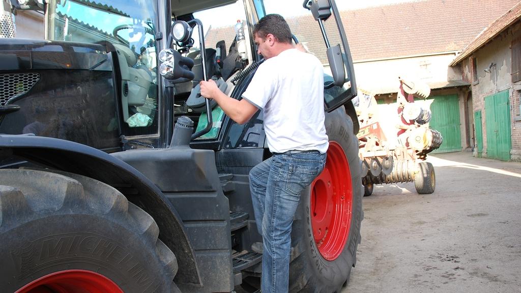 Mann steigt auf Traktor