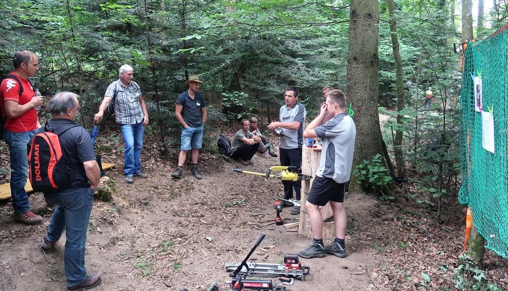 Bild: Mehrere Teilnehmer informieren sich zum Thema Fällkeile auf dem Waldsicherheitstag