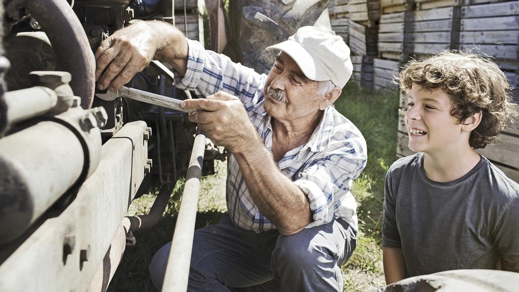 Senior mit Enkel beim Arbeiten