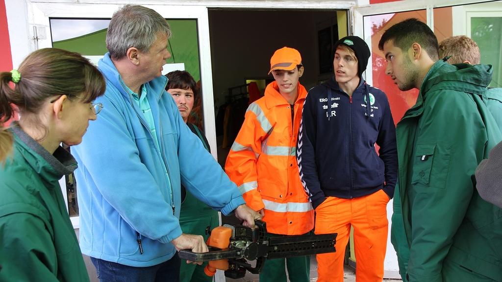 Mann zeigt jungen Menschen die Funktionsweise einer elektrischen Heckenschere