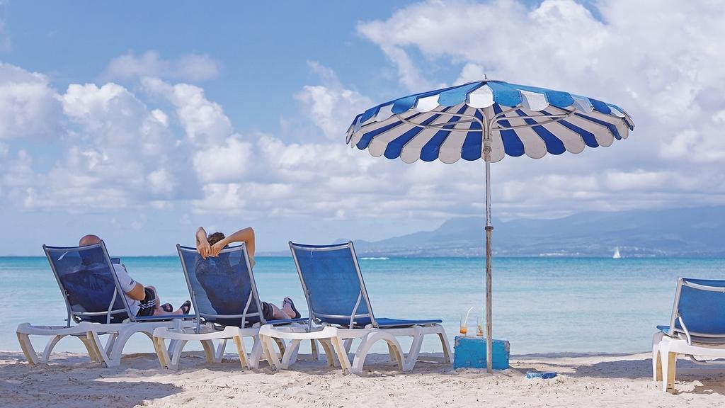 Strand mit Liegestühlen und Sonnenschirm. Auf zwei Liegestühlen liegen Personen.
