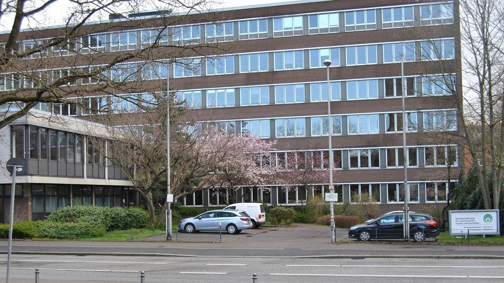Bürogebäude der SVLFG in Kiel, aufgenommen von der Straße, mit Blick auf Parkplatz im Vordergrund