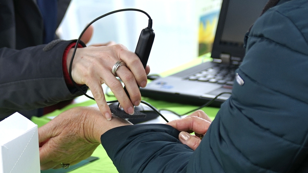 Am Arm wird mit einem UV-Messgerät diepersönliche Eigenschutzzeit der Haut unter Sonnenstrahlung gemessen