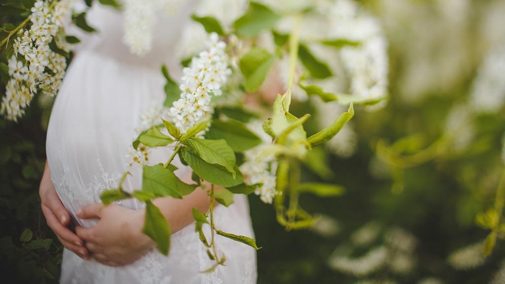 Schwangere Frau im weißen Kleid; sie steht hinter einer grünen Pflanze mit weißen Blüten