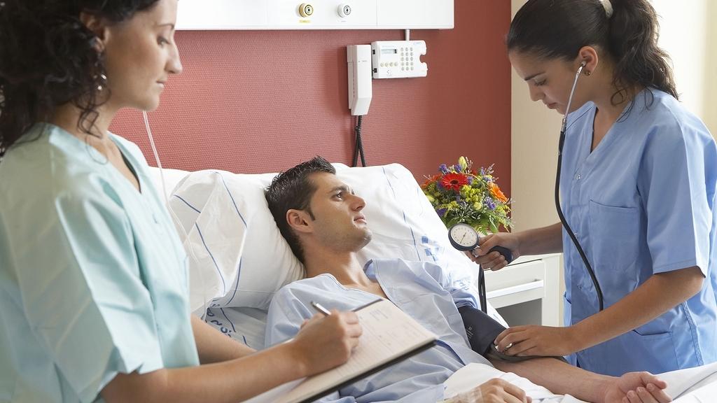 Krankenschwestern bei der 'Behandlung eines Patienten