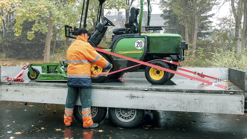 Eine Maschine, die auf einem Anhäger transportiert werden soll, wird mittels Zurrgurten durch den Fahrer gesichert.