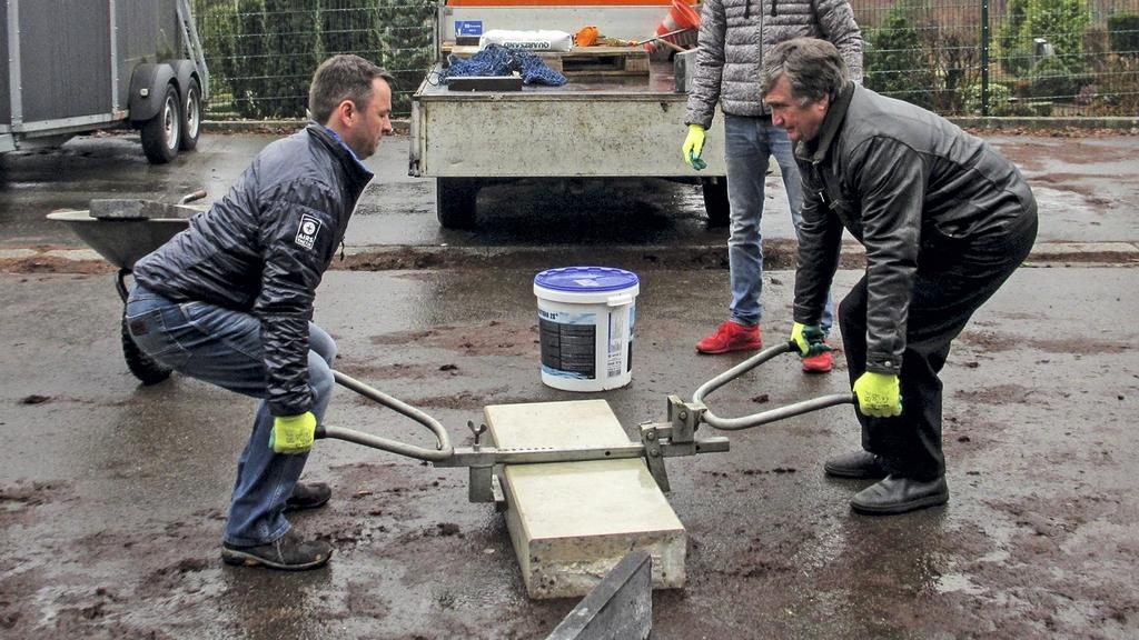 Zwei Männer heben einen großen Steinblock mit einer Hebehilfe an