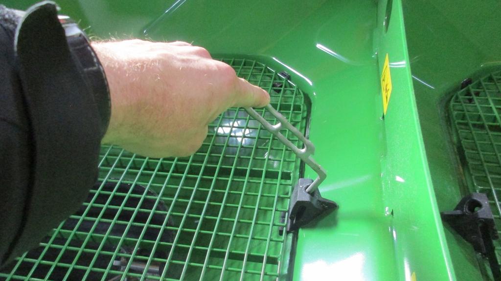 Eine Hand öffnet mit geeignetem Werkzeug ein Schutzgitter
