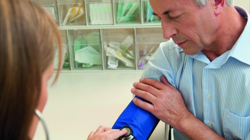 Frau misst bei einem männlichen Patienten den Blutdruck