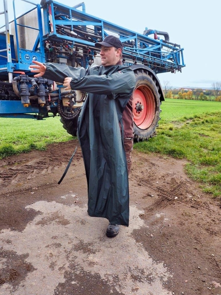 Bild: Mann vor Landmaschine beim Anziehen einer Ärmelschürze