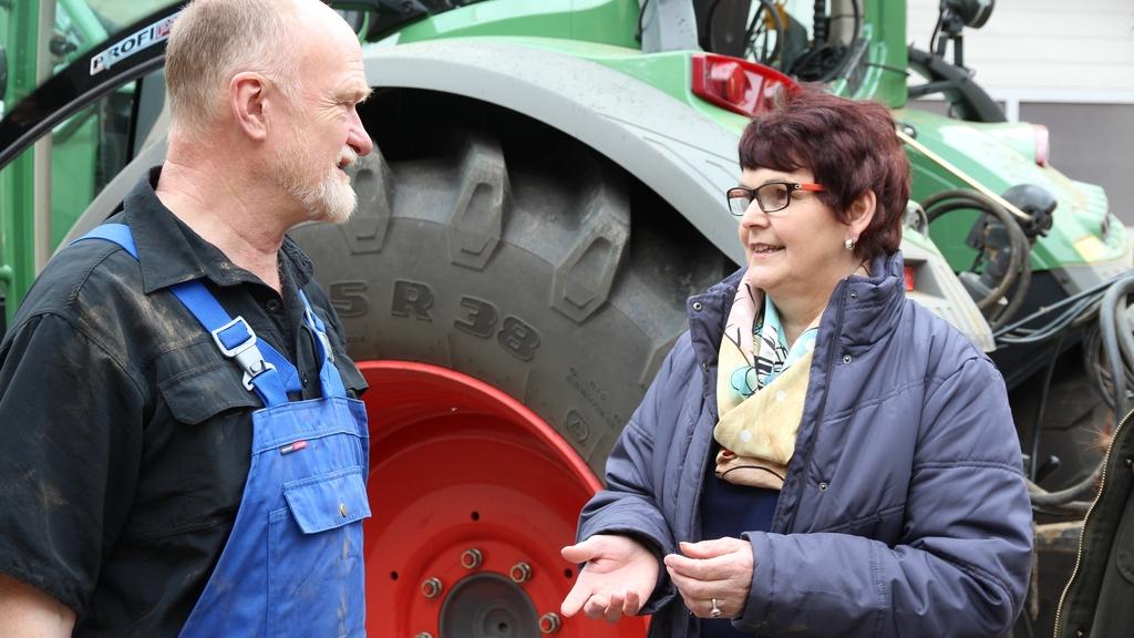 Ein Mann und eine Frau im Gespräch. Im Hintergrund ein Traktor