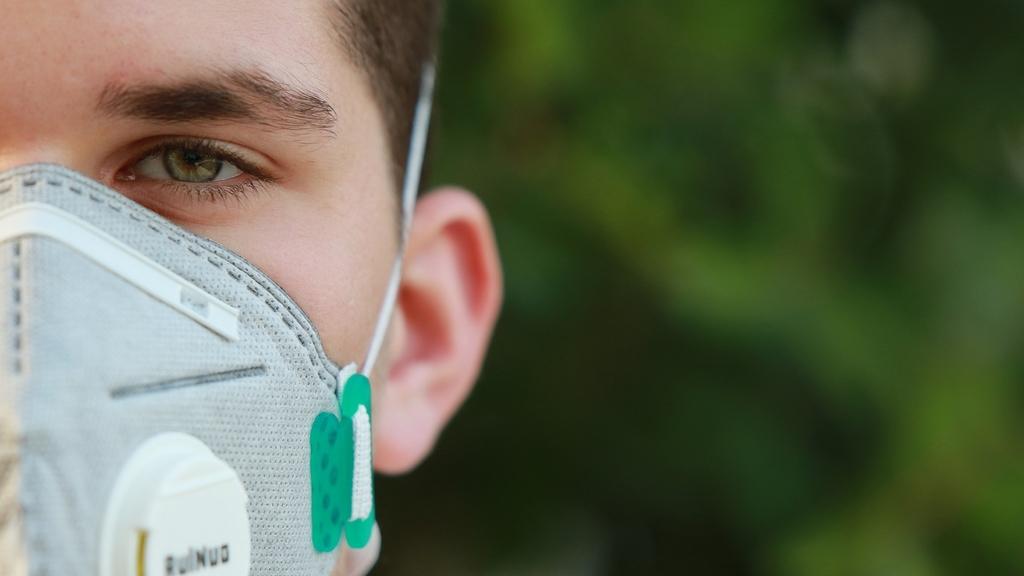 das halbe Profil eines jungen Mannes mit einer FFP3-Maske