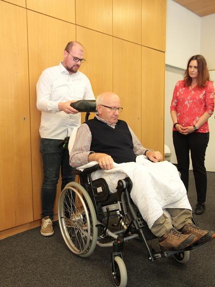 Ein Mann sitzt im Rollstuhl. Ein weiterer Mann steht hinter und eine Frau neben dem Rollstuhl.