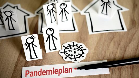 Stichmännchen, das Coronavirus und Häuser auf Papier gezeichnet auf dem Tisch liegend mit einem Stift