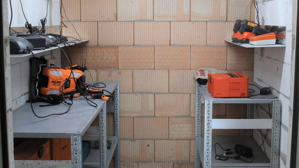 Kellerraum mit zwei Stahltischen, auf denen Ionen-Lithium-Akkus abgelegt sind.