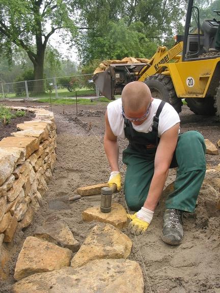 Bild: Arbeiter beim Befestigen von Natursteinen mit einem rückschlagarmen Hammer