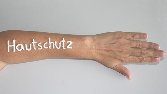 Auf dem Arm ist das Wort Hautschutz aufgeschrieben