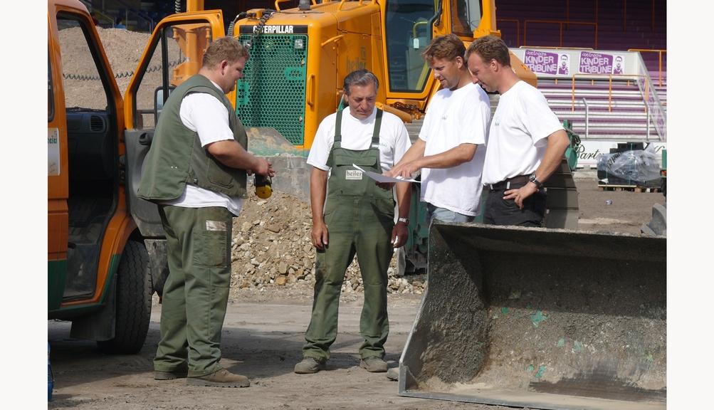 Bild: Vier Bauarbeiter bei einer Teambesprechung