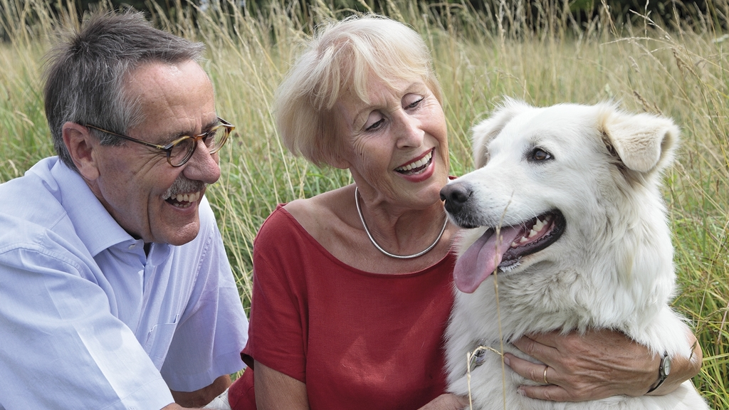 Senioren Ehepaar mit Hund im Feld