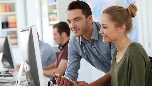 Studierende mit Ausbilder am Computer