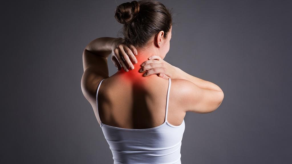 Frau in Unterhemd und Rückenansicht fasst sich mit beiden Händen an den schmerzenden Nacken. Nackenpartie ist rot markiert, was die brennenden Schmerzen bildlich darstellen soll.