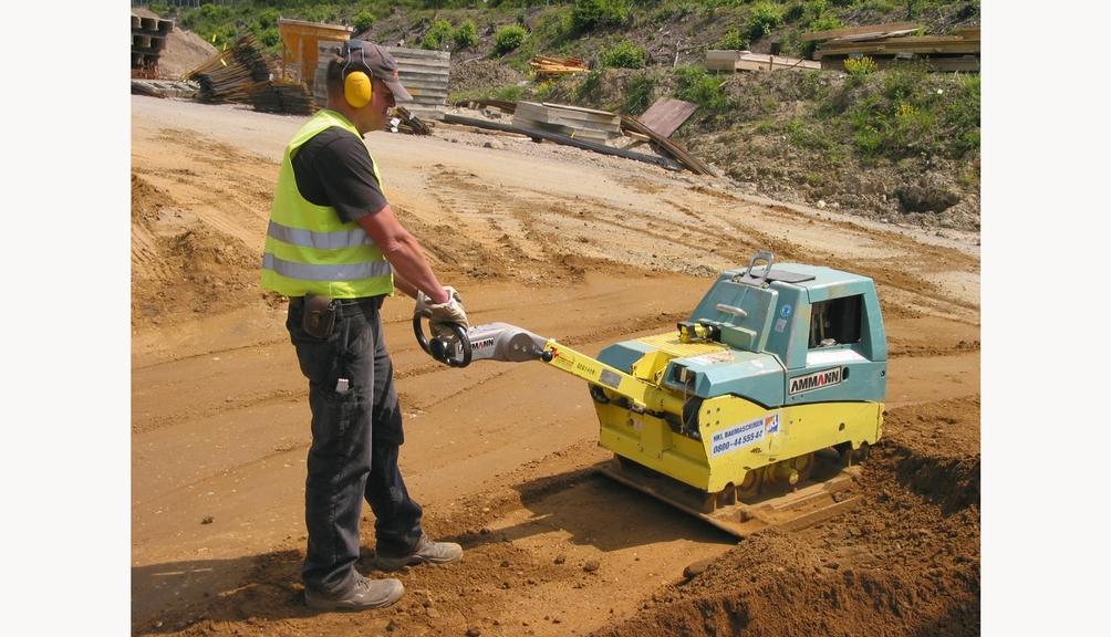 Bild: Arbeiter mit Körperschutzkleidung verdichtet Boden mit Rüttelplatte