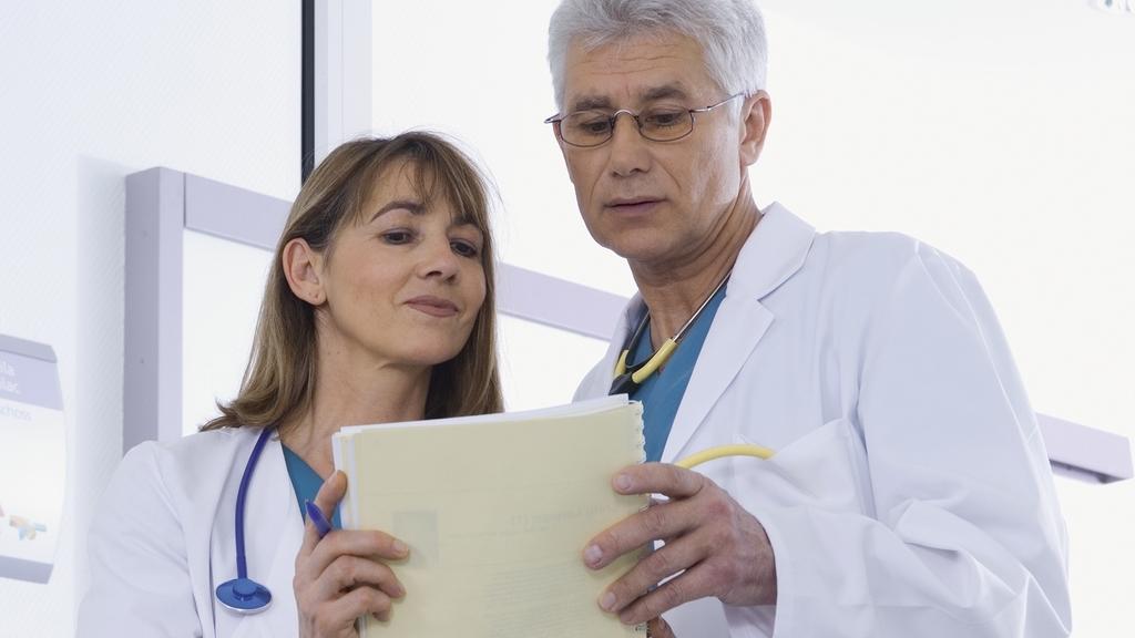 Ärztin und Arzt schauen sich Unterlagen an